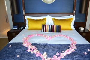 Heart of fresh roses petals on the bed
